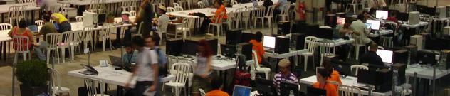 Computadores, cadeiras e pessoas no primeiro dia do Campus Party 2009