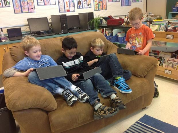 Crianças mexendo em iPads no sofá